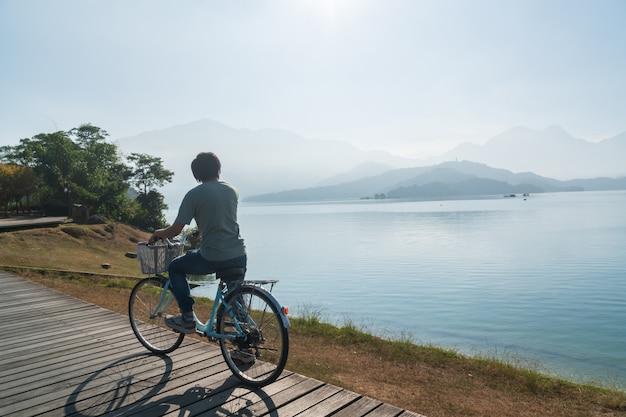 Jonge mannen fietsen op fietspad bij het meer in de ochtend. actieve mensen. buitenshuis Premium Foto