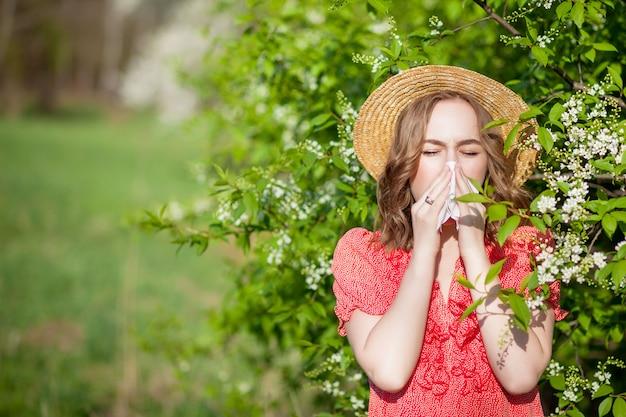 Jonge meisjes blazende neus en het niezen in weefsel voor bloeiende boom. seizoensgebonden allergenen die mensen treffen. mooie dame heeft rhinitis. Premium Foto