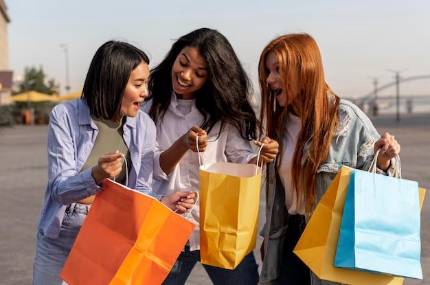 Jonge meisjes die een wandeling maken na het buiten winkelen Gratis Foto