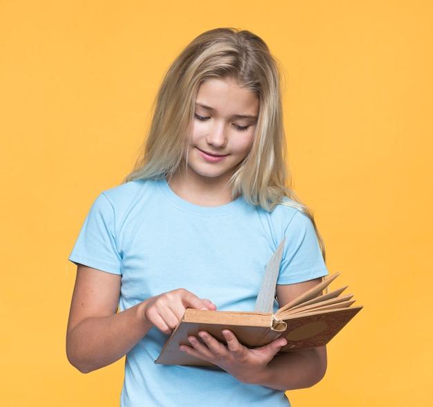 Jonge meisjeslezing met gele achtergrond Gratis Foto