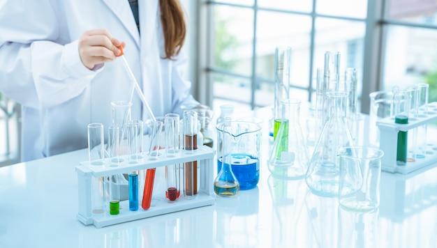 Jonge meisjeswetenschapper die experimenten chemisch in glazen buis maken in de laboratoriumruimte Premium Foto