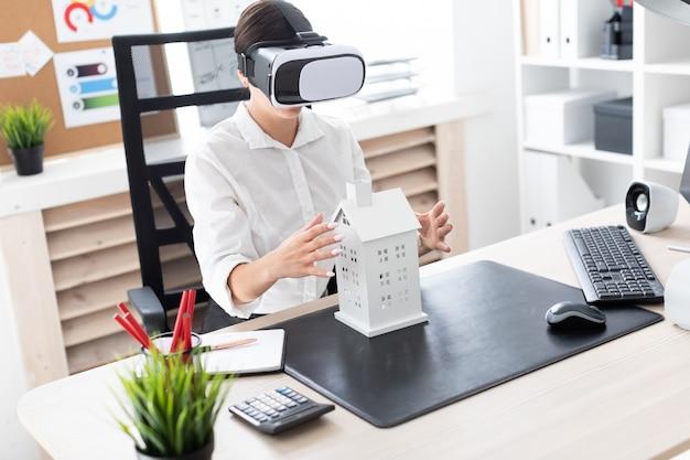 Jonge meisjeszitting in virtuele werkelijkheidsglazen. voor haar op tafel staat de indeling van het huis. Premium Foto
