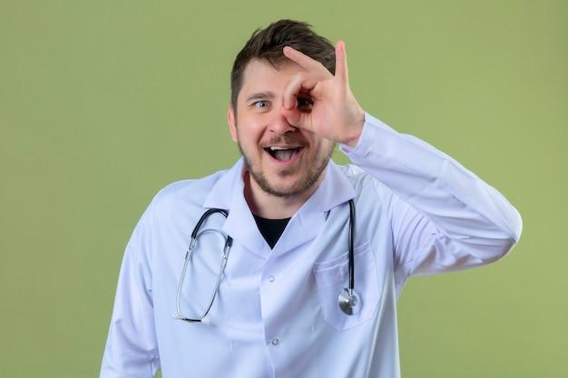 Jonge mens arts witte laag dragen en stethoscoop die ok teken met hand doen en vingers die door teken met grote glimlach over geïsoleerde groene achtergrond kijken Gratis Foto