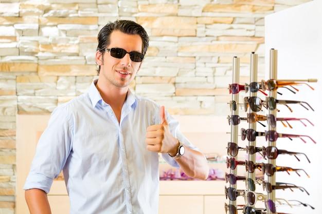 Jonge mens bij opticien het kopen zonglazen Premium Foto
