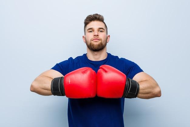 Jonge mens die bokshandschoenen draagt Premium Foto