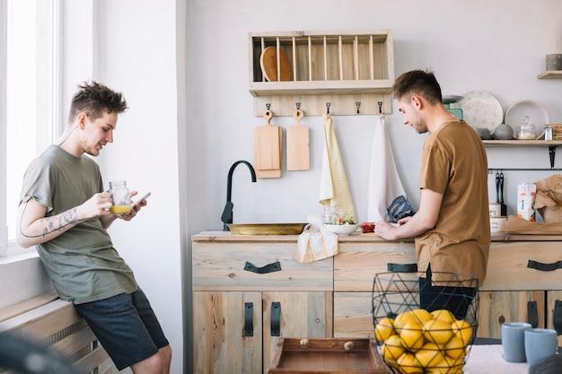 Jonge mens die cellphone gebruiken terwijl zijn vriend die voedsel in keuken voorbereidt Gratis Foto