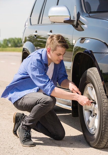 Jonge mens die de lekke band op zijn auto verandert. Premium Foto