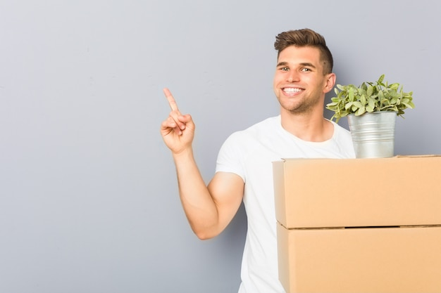 Jonge mens die een dozen doen die van de bewegingsholding vrolijk het richten met weg wijsvinger glimlachen. Premium Foto