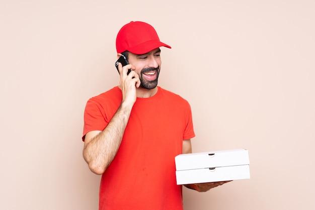 Jonge mens die een pizza houdt die een gesprek met de mobiele telefoon houdt Premium Foto