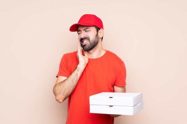 Jonge mens die een pizza houdt over geïsoleerd met tandpijn Premium Foto