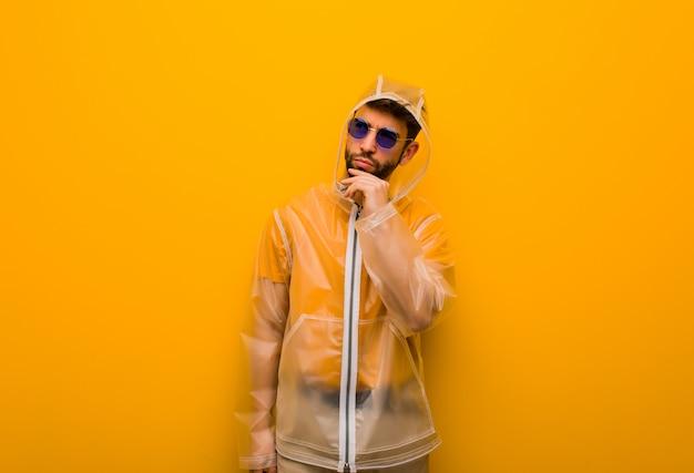 Jonge mens die een regenjas draagt die over een idee denkt Premium Foto