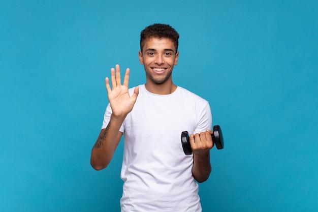 Jonge mens die een sumbbell opheft die vriendelijk glimlacht en kijkt, nummer vijf of vijfde met vooruit hand toont, aftellend Premium Foto