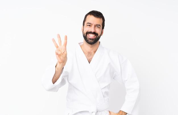 Jonge mens die karate gelukkig doet en drie met vingers telt Premium Foto