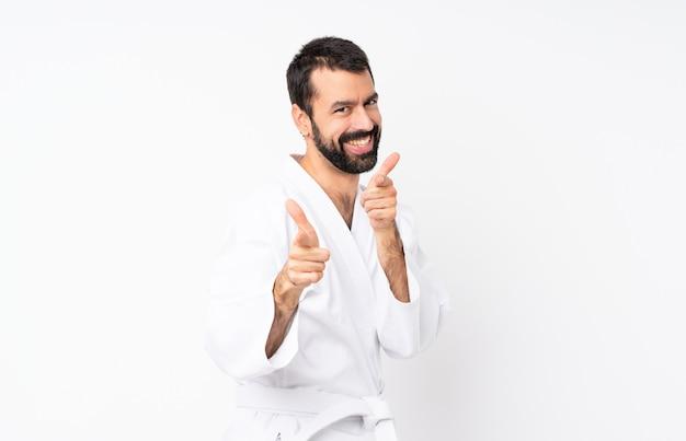 Jonge mens die karate over geïsoleerd wit doet die aan de voorzijde en het glimlachen richten Premium Foto
