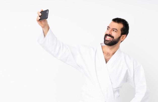 Jonge mens die karate over geïsoleerd wit doet die een selfie maken Premium Foto