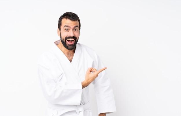 Jonge mens die karate over geïsoleerd wit doet verrast en kant richt Premium Foto