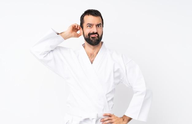 Jonge mens die karate over geïsoleerde witte muur doet die twijfels heeft Premium Foto