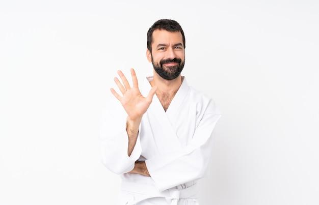 Jonge mens die karate over geïsoleerde witte muur doet die vijf met vingers telt Premium Foto