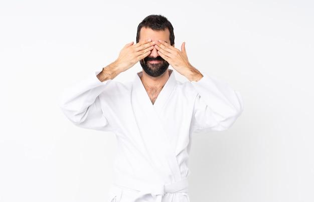 Jonge mens die karate over wit doet dat ogen behandelt door handen Premium Foto