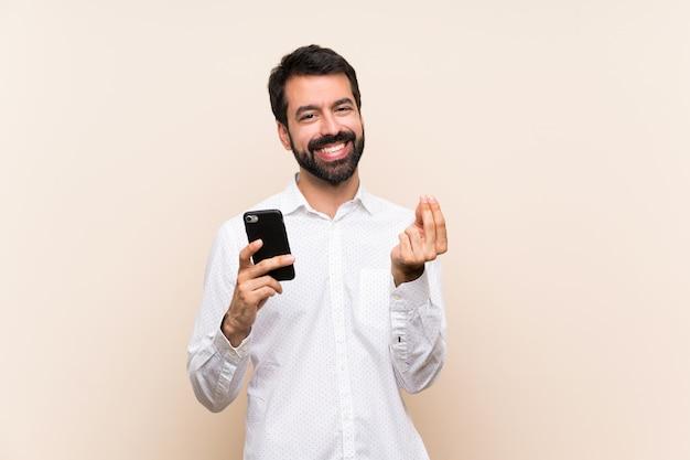 Jonge mens die met baard mobiel het maken van geldgebaar houdt Premium Foto