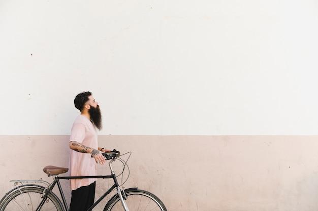 Jonge mens die met fiets tegen geschilderde muur loopt Gratis Foto