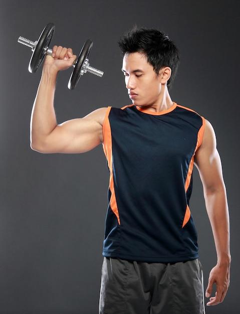 Jonge mens die met gewichtheffen uitoefenen Premium Foto