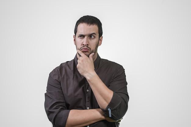 Jonge mens die met zijn hand op zijn gezicht en overhemd denkt Premium Foto