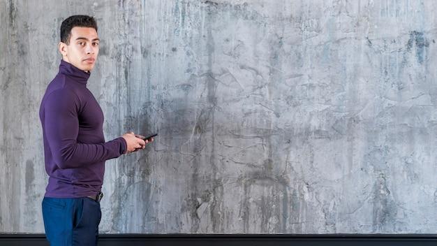 Jonge mens die mobiele telefoon met behulp van die camera bekijken die zich tegen concrete grijze muur bevinden Gratis Foto