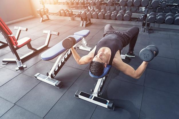 Jonge mens die oefening voor abs spieren in gymnastiek maakt. Premium Foto