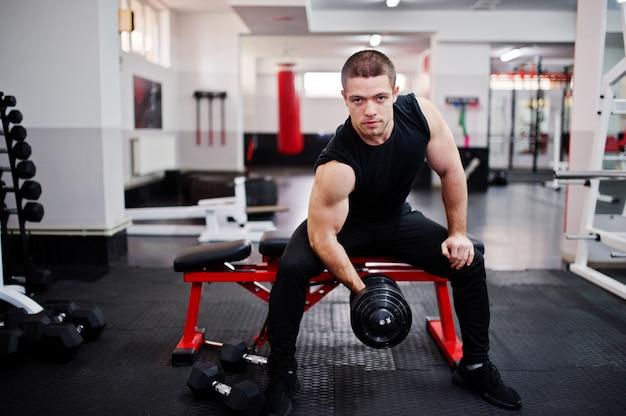 Jonge mens die oefeningen doet en hard in gymnastiek werkt en van zijn opleidingsproces geniet. Premium Foto