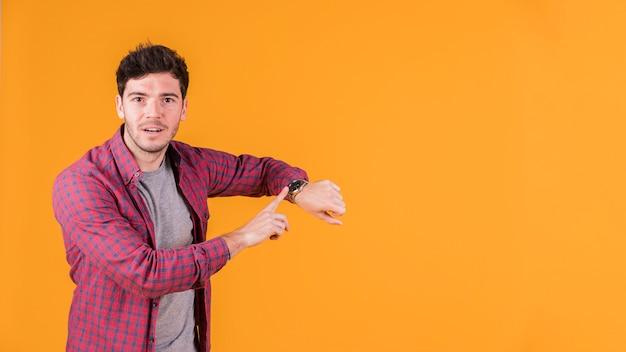 Jonge mens die op polshorloge richt en camera tegen oranje achtergrond bekijkt Gratis Foto