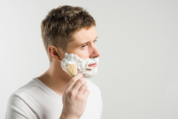 Jonge mens die schuim op wangen met borstel over witte achtergrond toepast Gratis Foto