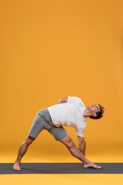 Jonge mens die uitrekkende oefening op yogamat doet Gratis Foto