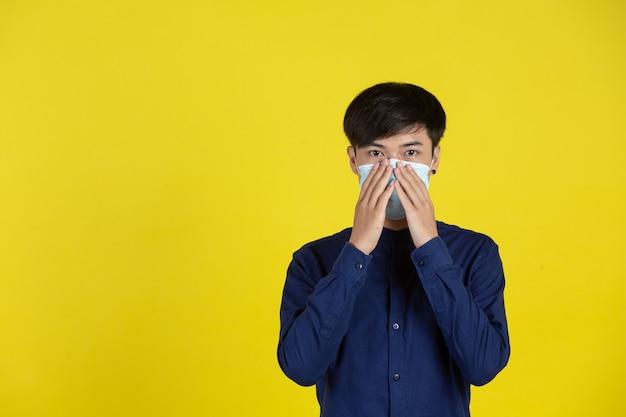 Jonge mens die wegwerp medisch masker draagt dat zich voor gele muur bevindt Gratis Foto