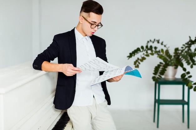 Jonge mens die zich dichtbij de piano bevindt die muzikaal blad bekijkt Gratis Foto