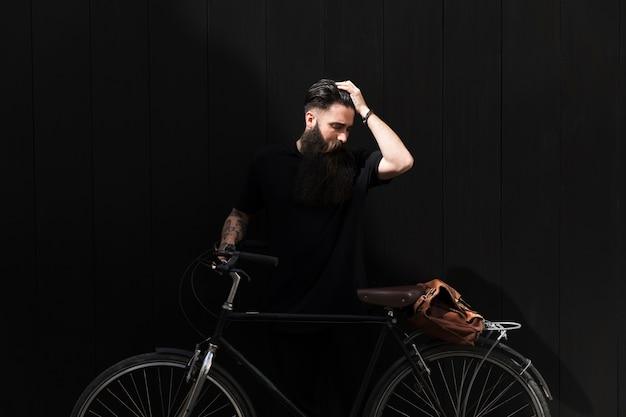 Jonge mens die zich dichtbij fiets met zijn hand op hoofd tegen zwarte achtergrond bevindt Gratis Foto