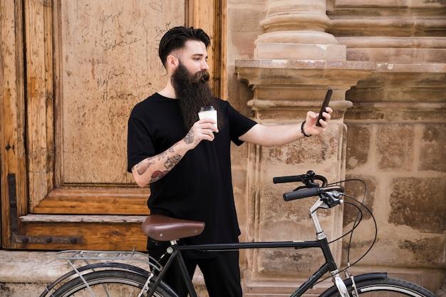 Jonge mens die zich met fiets voor houten deur bevindt die selfie op mobiele telefoon neemt Gratis Foto