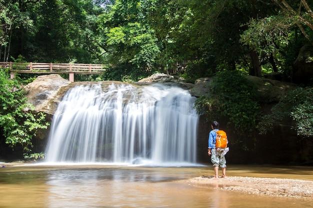 Jonge mens die zich voor waterval bevindt die waterval en reisrugzak bekijkt in thailand Premium Foto