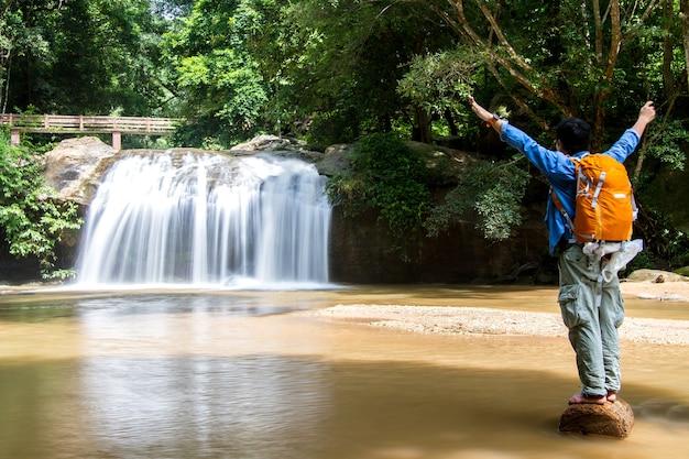 Jonge mens die zich voor waterval met hand het uitgestrekte bekijken waterval bevinden Premium Foto