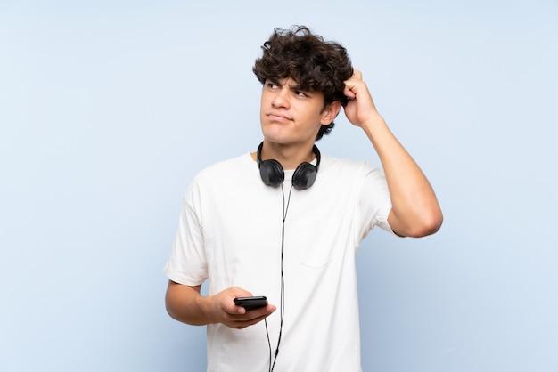 Jonge mens het luisteren muziek met mobiel over geïsoleerde blauwe muur die twijfels hebben en met verwarren gezichtsuitdrukking Premium Foto