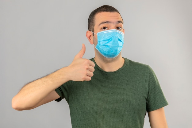 Jonge mens in medisch masker die ok teken, duim omhoog met vingers doen die op wit worden geïsoleerd Gratis Foto