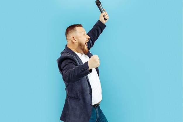 Jonge mens met microfoon op blauwe achtergrond, belangrijk concept Gratis Foto