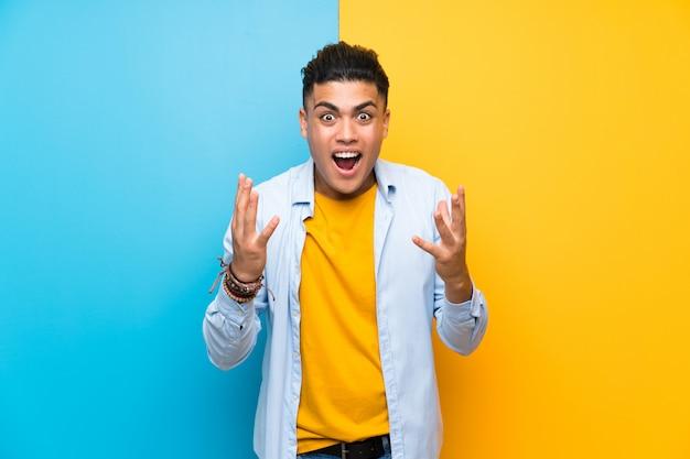 Jonge mens over geïsoleerde kleurrijk met verrassingsgelaatsuitdrukking Premium Foto