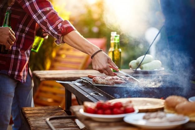 Jonge mensen die barbecue bij de grill in plattelandshuisje roosteren. Gratis Foto
