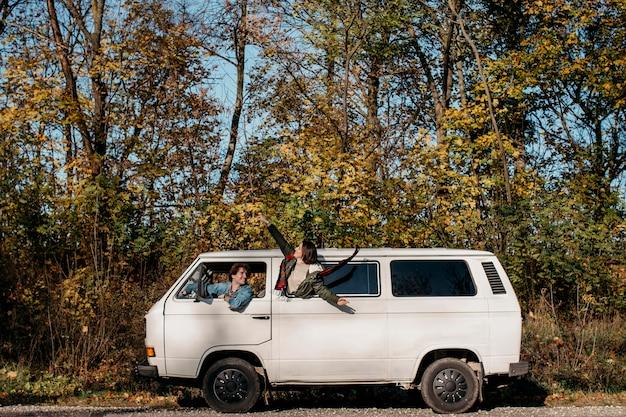 Jonge mensen die een roadtrip maken in een wit busje Gratis Foto