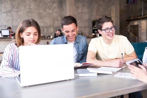 Jonge mensen die op laptop werken Gratis Foto