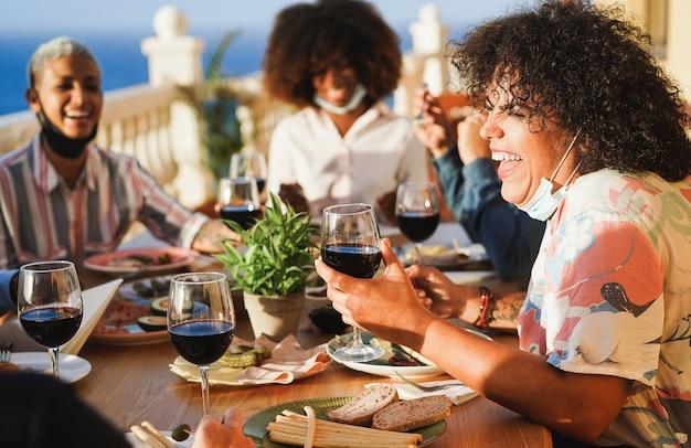 Jonge mensen die rode wijn eten en drinken terwijl ze beschermende maskers dragen Premium Foto