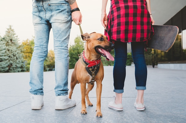 Jonge mensen in stedelijke scène lopen de hond. jonge man met een hond aan de leiband en jonge vrouw met een skateboard buitenshuis - concept van jeugdcultuur mensen die verantwoordelijk zijn en een huisdier hebben Premium Foto