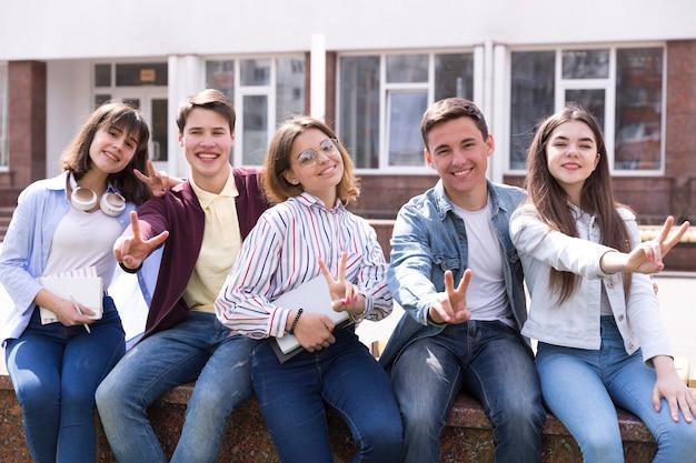 Jonge mensen zitten met boeken en twee vingers gebaren Gratis Foto