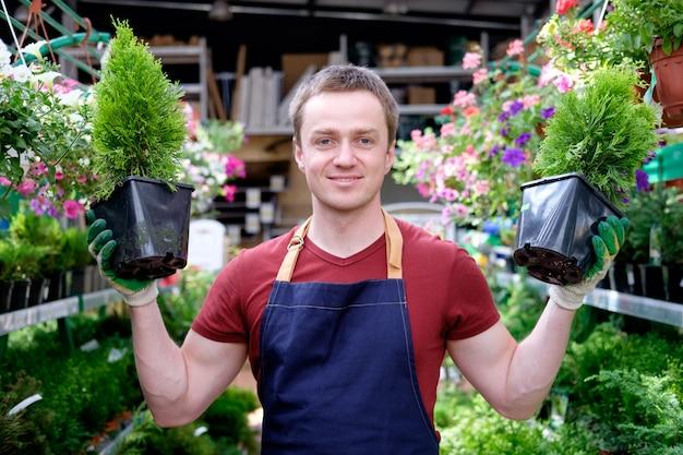 Jonge mensenarbeider in de serre van de installatiemarkt op het werk Premium Foto